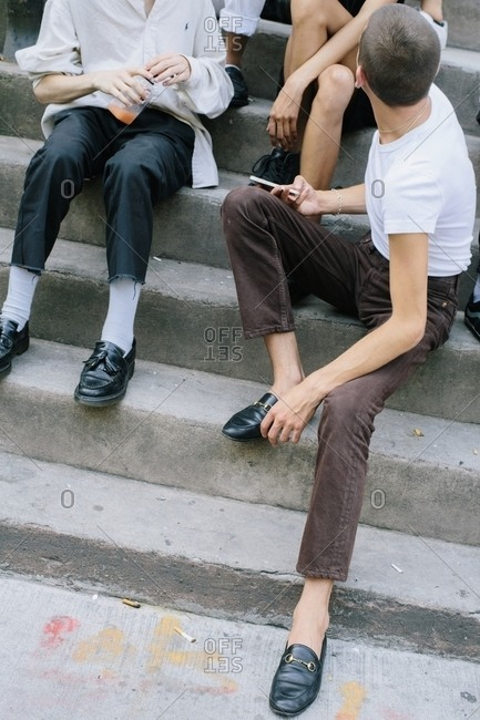 Men in skinny pants and loafers hanging out on steps