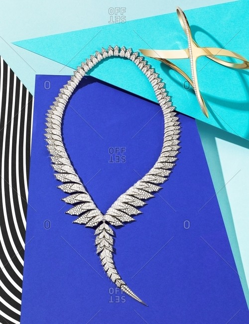 Necklace in the shape of a bird's tail and gold geometric bracelet