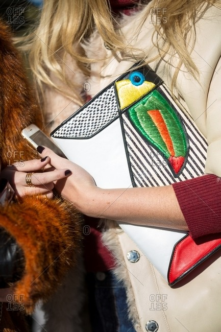 Woman holding a toucan patterned clutch purse