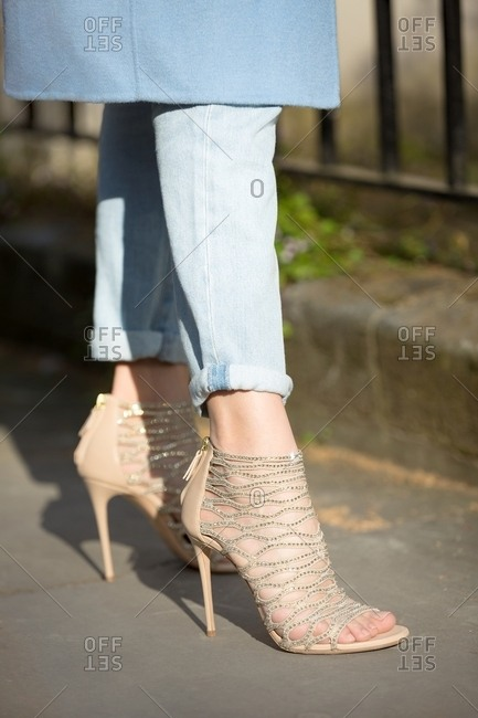 Woman in jeans and beige high heel sandals