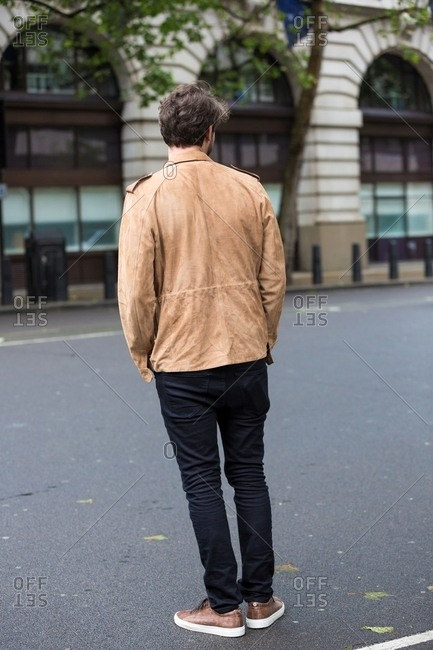 Man in a tan leather jacket and black pants crossing a street