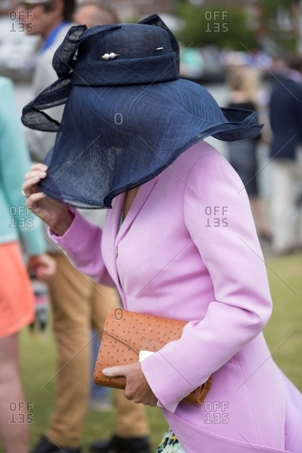 Woman in a pink coat and navy blue hat with veil