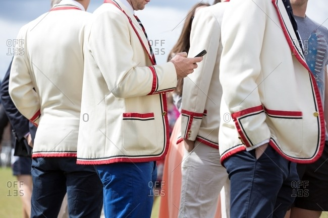 Group of men in white suit jackets with red trim