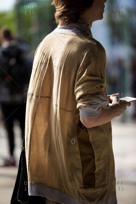 Man in a light beige jacket holding his cellphone
