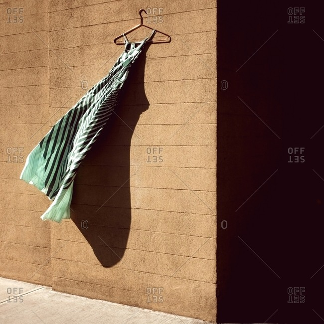 Green striped dress hanging on the side of a brick building