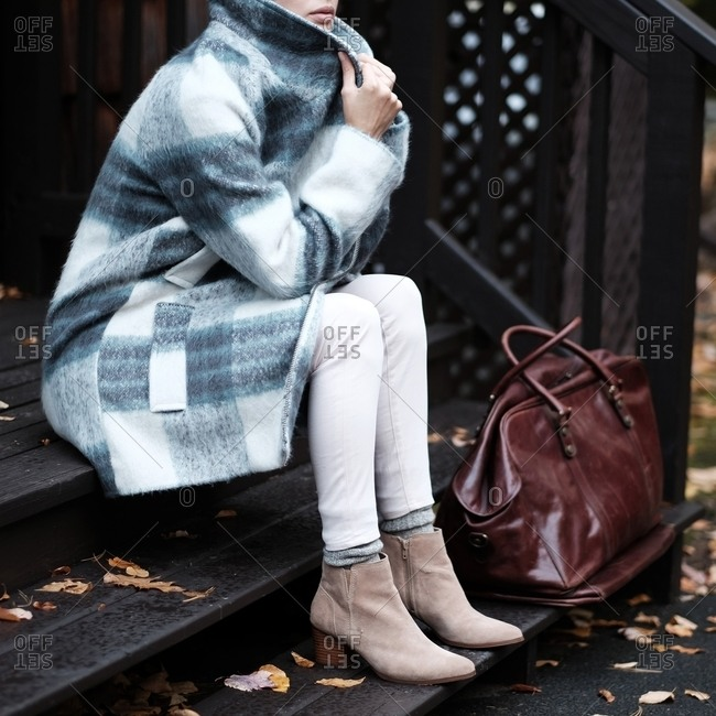 Woman in a plaid fleece jacket and beige boots sitting on steps