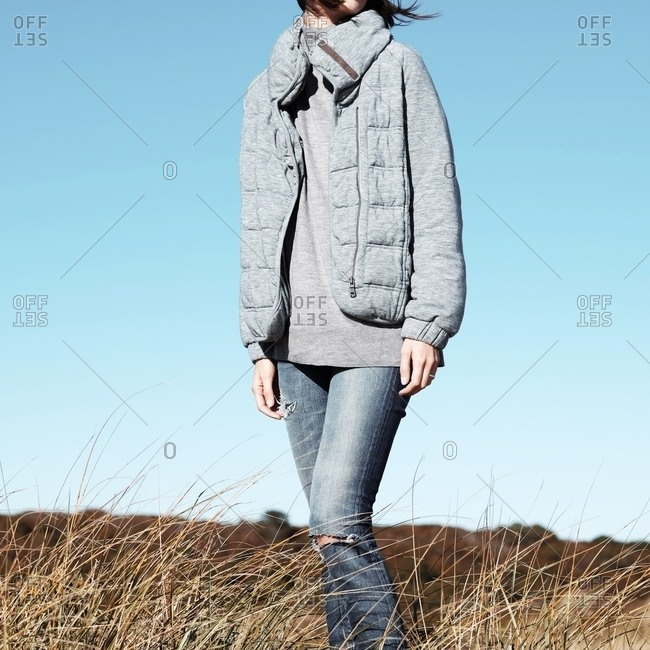 Woman in a gray jacket and jeans standing in a field