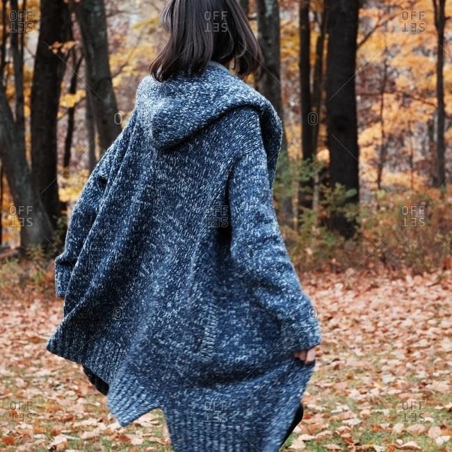 Woman in a long blue cardigan walking in autumn leaves
