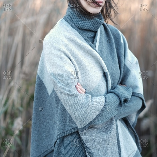 Woman in a gray turtleneck sweater and shawl in a field