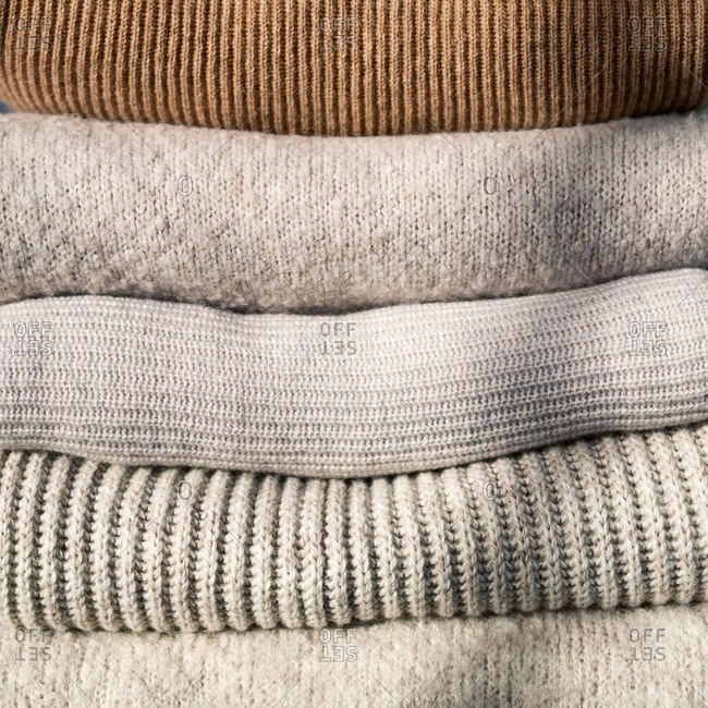 Pile of folded neutral-colored sweaters