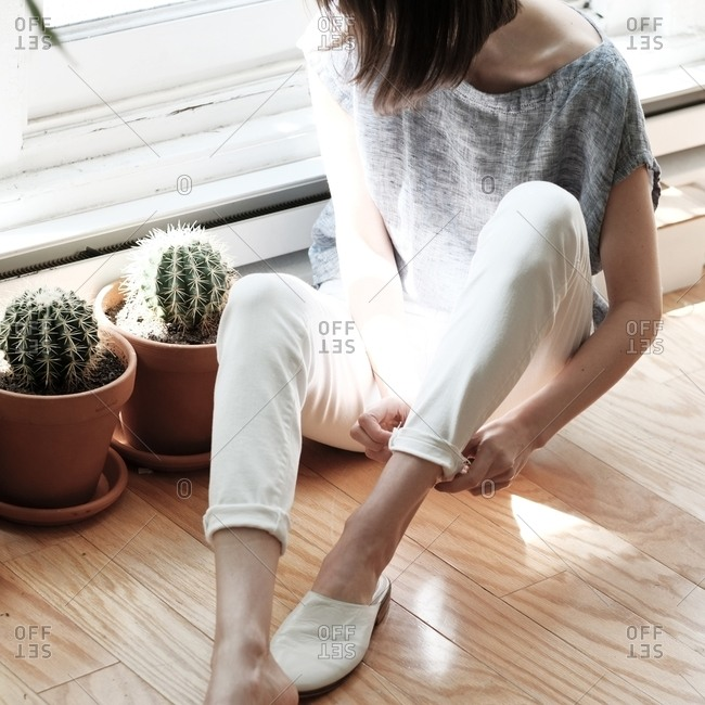 Woman rolling up the cuffs of her pants next to cactus plants