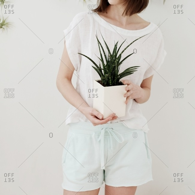 Woman in a white t-shirt and shorts holding a potted plant