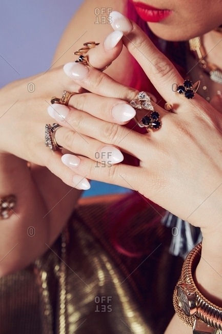 Interlaced hands of a woman with painted nails and rings