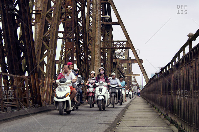 Hanoi, Vietnam - October 13, 2016: Scooters driving on a bridge in Hanoi