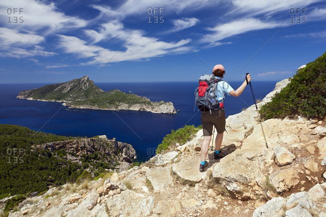 A woman walks in the mountainous country above Sant Elm, Majorca, Balearic Islands, Spain