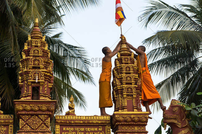 Siem Reap, Cambodia - October 13, 2016: Two monks put flag on a tower in Siem Reap, Cambodia