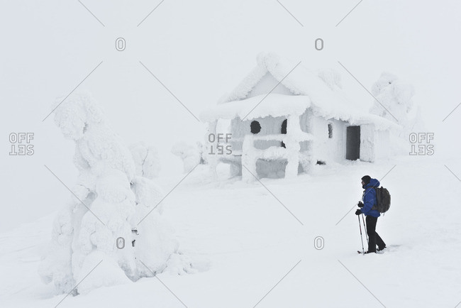 Levi, Finland - October 13, 2016: Man trekking through snow covered hills with house in Levi, Finland