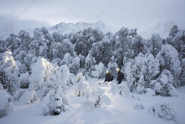 Lyngen Alps, Norway - October 13, 2016: Men trekking through deep snow in the Lyngen Alps, Norway