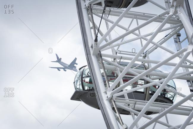 London, England - October 15, 2016: Plane flying over the London Eye