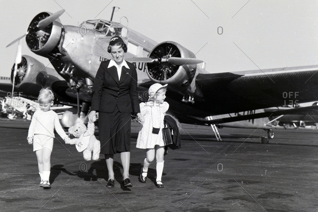 Germany - 1930s: A stewardess leads two children above the airfield to the airplane in Germany in the 1930s