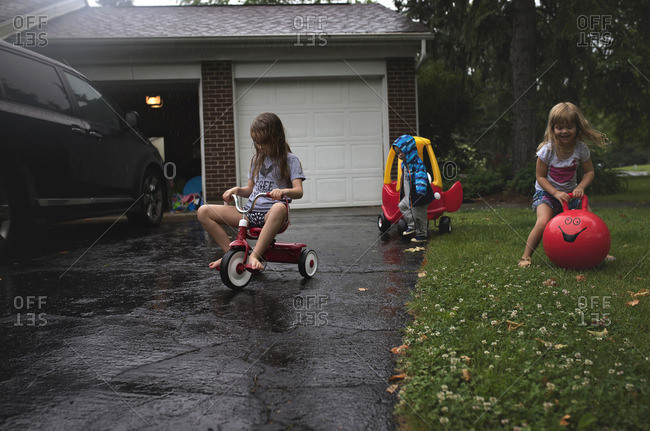 Three siblings playing together near a driveway