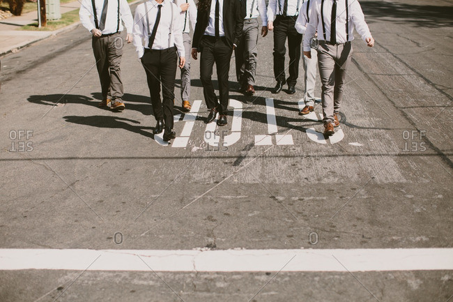 Groom and groomsmen walking on a city street