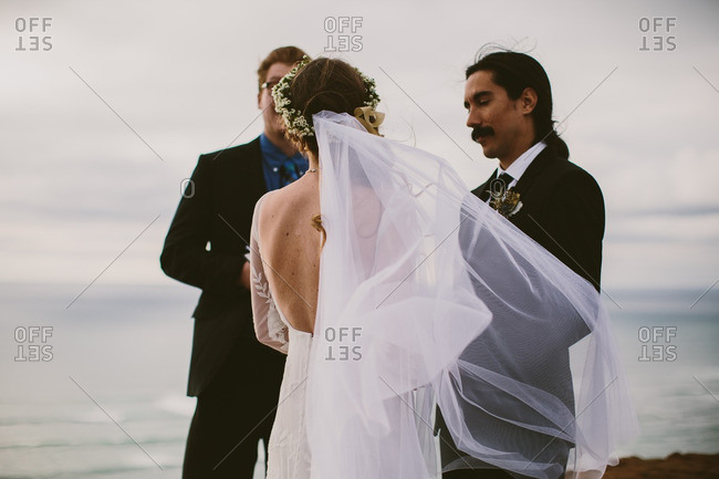 Couple being married by a pastor on a beach