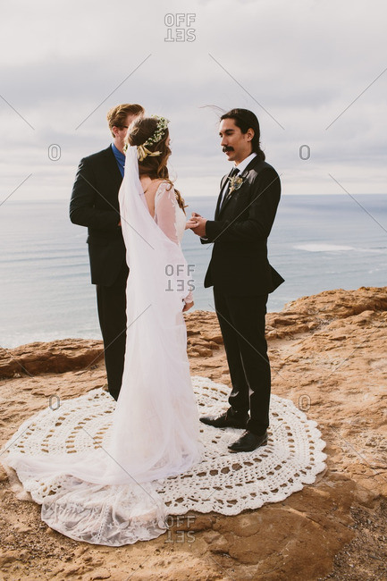 Man and woman being married by a pastor on a beach