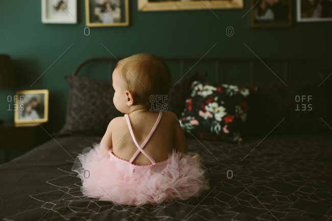 Toddler in pink tutu on bed