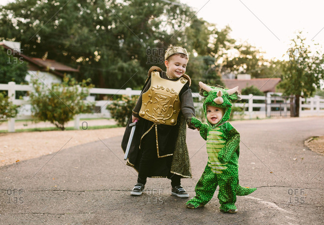 Boy and toddler in costumes in street