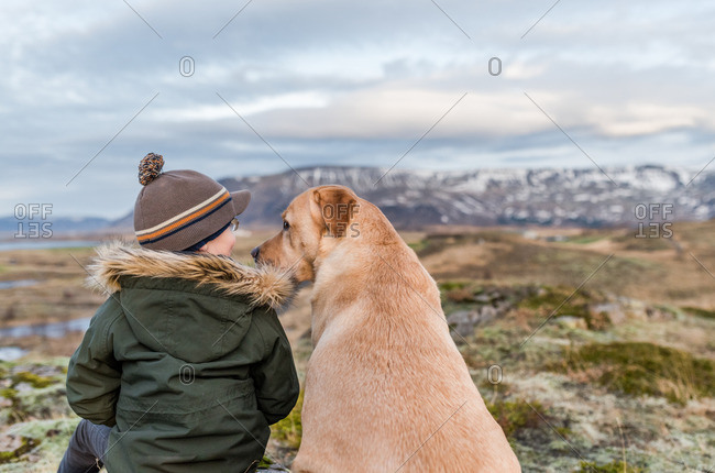 Boy and his dog sitting in a vast field near mountains