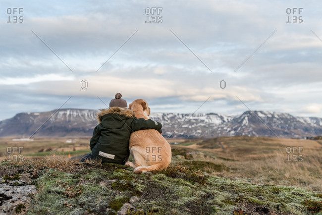 Boy sitting with his arm around his dog taking in a mountain view