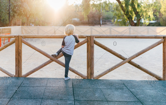 Boy standing at a wooden playground fence
