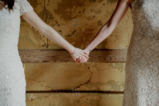 Two brides holding hands against rustic wall