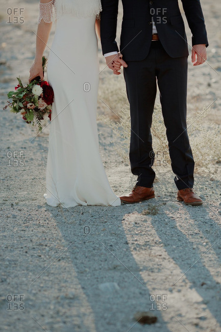 Backlit view of bride and groom holding hands and casting long shadows