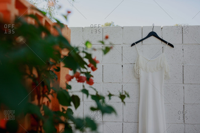 Wedding gown with crochet lace ruffle handing on garden wall