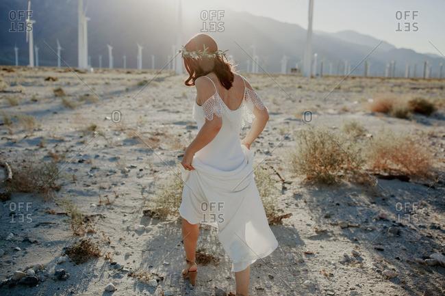 Bride walking in desert  near wind turbines