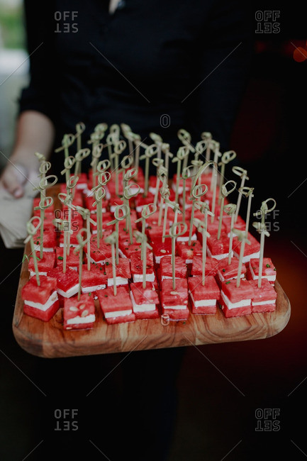 Server with tray of watermelon and cheese hors d'ouvres