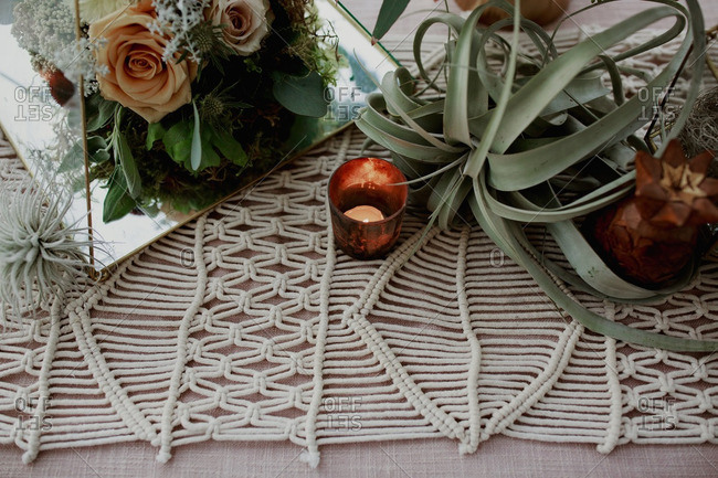 Macrame table runner with candle and flower arrangements