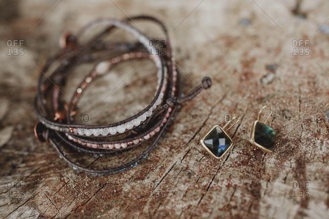 Beaded leather bracelet with gemstone earrings on log