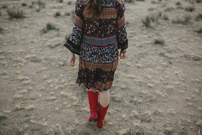 Woman in dress and red cowboy boots in desert