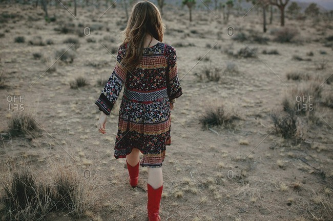 Woman in flowered dress and red cowboy boots in desert