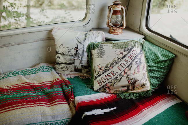 Vintage pillows and woven blankets in trailer camper