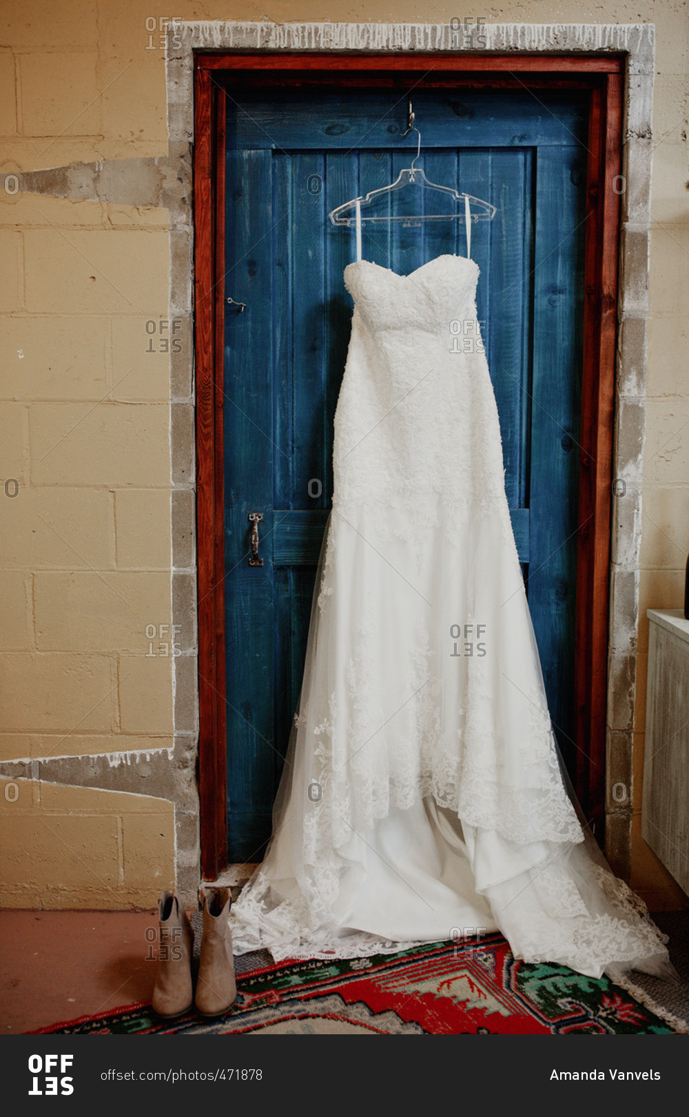 Lace Wedding Dress Hanging From Hook On Blue Door