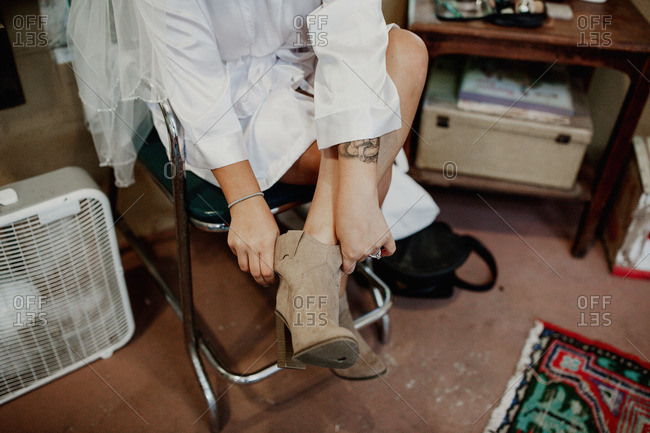 Seated woman putting on cowboy boots