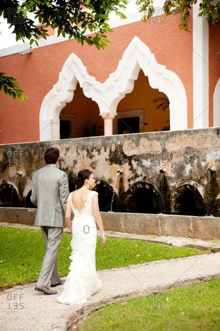 Yucatan, Mexico - June 26, 2011: Bride and groom walking towards a red and white hacienda in Yucatan