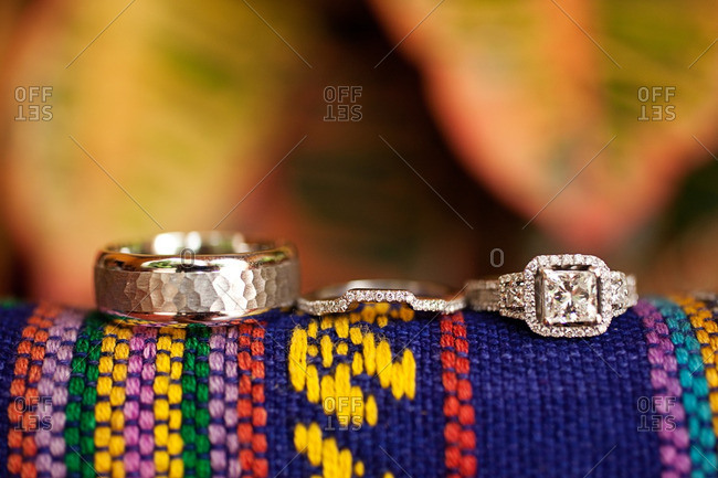 Wedding bands on a colorful woven fabric