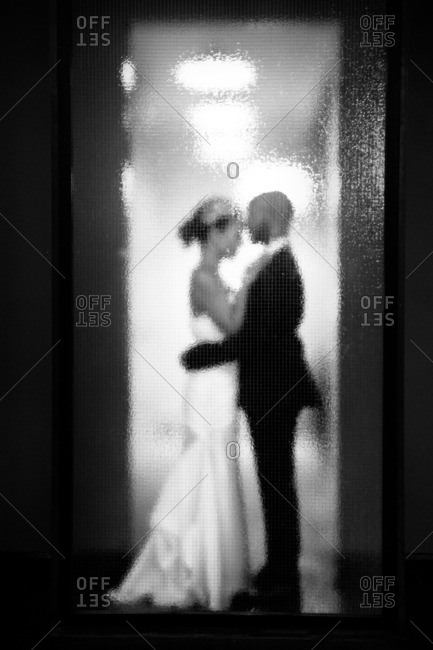 Bride and groom standing behind blurry glass in black and white