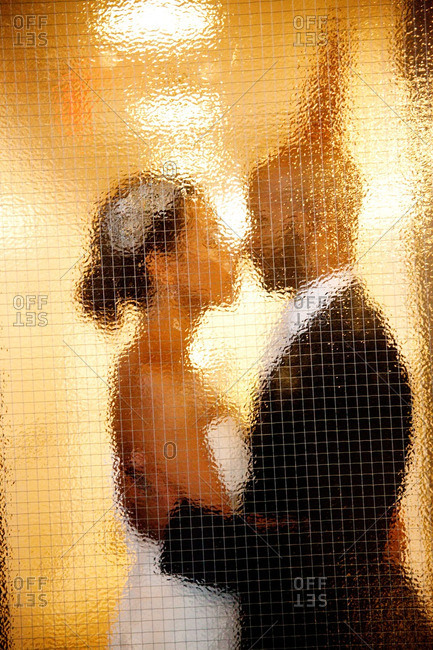 Bride and groom standing behind blurry glass