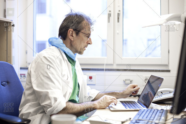 Doctor using laptop in office